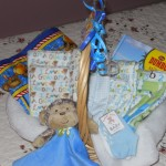 "Item # 25 ""Welcome Baby Boy"" (construction quilt, 2 baby socks, 2 receiving blankets & ""ILove Mommy & Daddy"" and ""I love Grammy"" burp cloths, monkey cuddle blanket & book) donated by  Alison Dupuis, valued at $80, opening bid $40"
